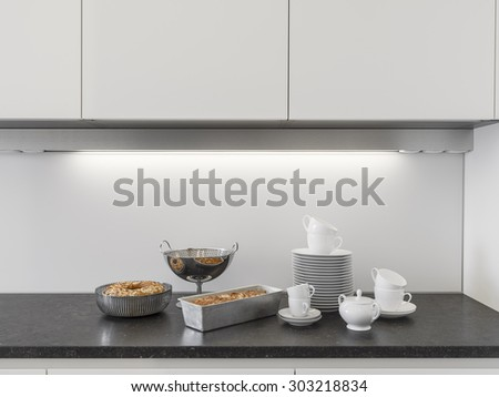 detail of dishes and cakes on the worktop in the modern kitchen - stock photo
