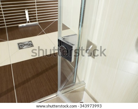 Detail of door hinge in beige and brown bathroom