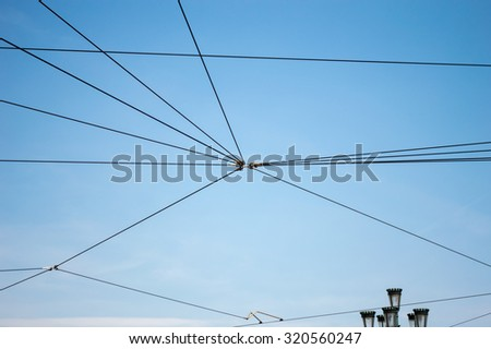 detail of electric cable for the tram of the city over blue sky and streetlamp in the background