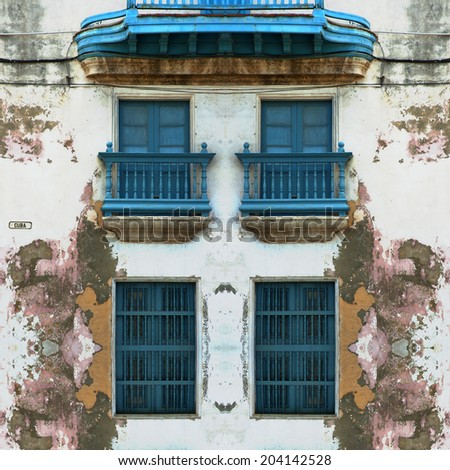 Detail of eroded Old Havana facade with blue windows - stock photo