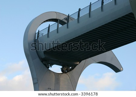Detail of Falkirk Wheel (rotating boat lift for canal boats between the Forth and Clyde Canal and the Union Canal, Scotland, UK, against cloudy sky. - stock photo