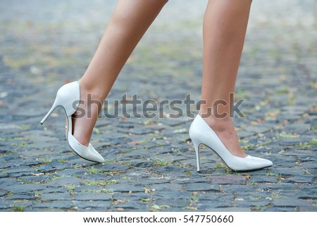 Detail of fashion woman in high heel white shoes on the city street .