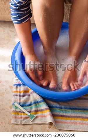 Detail of female legs in soap bath. - stock photo