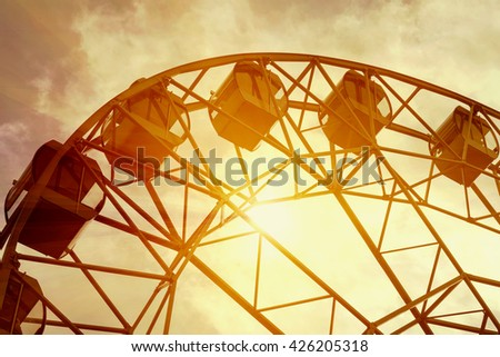 Detail of Ferris wheel and the bright sun. Toned - stock photo