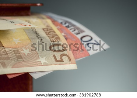 Detail of fifty euro banknote sticking out of a metal moneybox - stock photo
