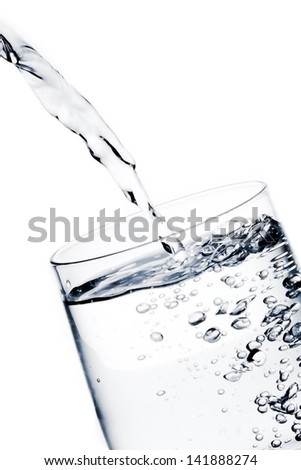 detail of filling a glass with pure water with bubbles on white background - stock photo