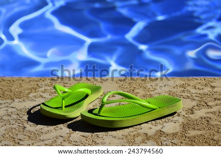 Detail of flip flops sandals by swimming pool - stock photo