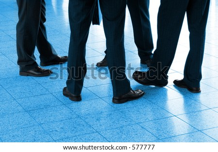 Detail of four businessmen in the circle, blue toned - stock photo