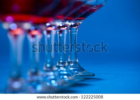 Detail of glasses filled with red wine over blue background. - stock photo