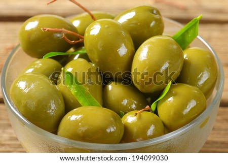 detail of glossy green olives in the glass bowl - stock photo