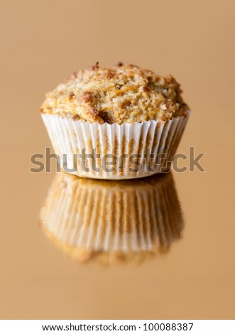 Detail of gluten free muffin with nuts on golden background