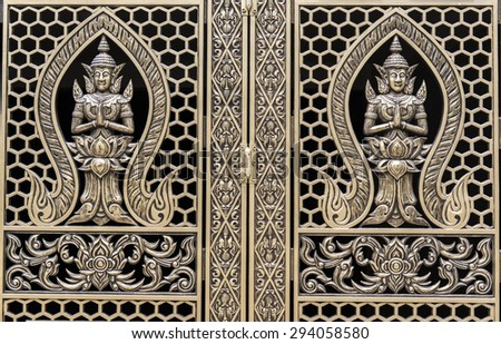 Detail of golden embossed doors in a Buddhist temple