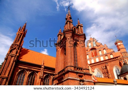 Detail of gothic St. Anne's Church and the Church of St. Francis from Assisi (Historical-architectural ensemble of Bernardines), Vilnius, Lithuania on blue sky background. Selective focus - stock photo
