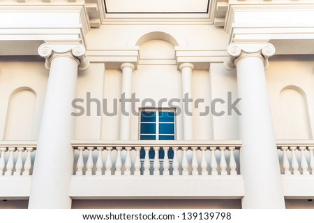 Detail of grand white building in classic style with balcony, square window and two big columns. Arch over window and from both sides from it. Architecture and facade of buildings. - stock photo