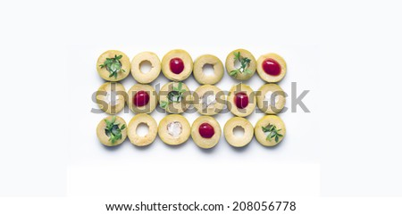 Detail of green olives with salt, ketchup and herbs on a white background. - stock photo