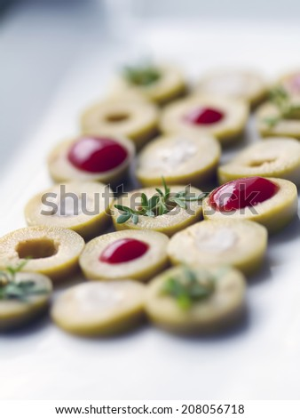 Detail of green olives with salt, ketchup and herbs on a white plate. - stock photo