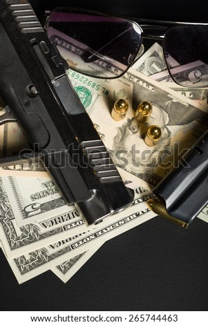detail of gun with bullet on US dollar banknotes, crime or corruption concept