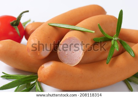detail of halved sausages with vegetable and herbs - stock photo