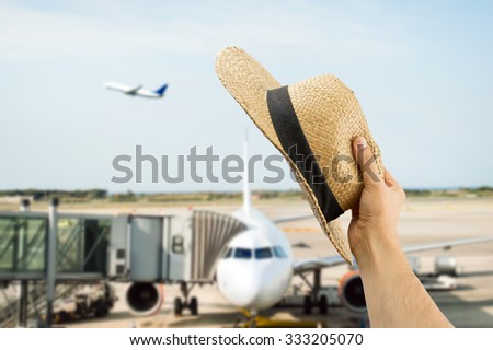 detail of hand holding the hat gesturing the greeting to the people of the flight of plane - stock photo
