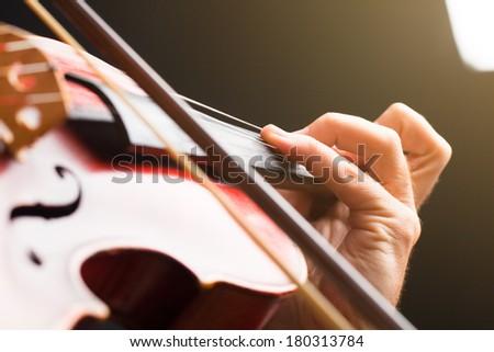 Detail of hand playing violin. Macro. Soft focus. - stock photo