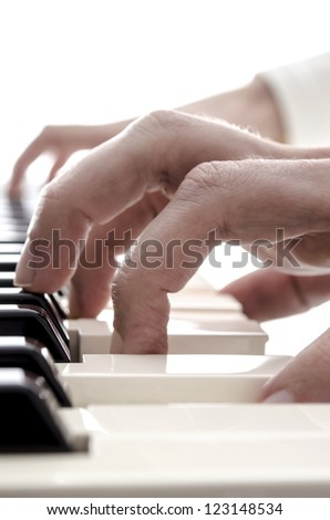 Detail of hands playing on digital piano keys.