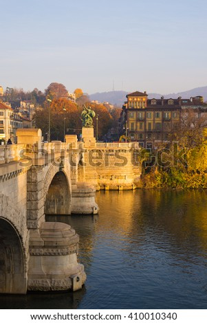 Detail of historical stone brigde in Torino (Turin - Italy) at sunset. Shot in autumn season, colorful trees on the banks of Po River. Clear sky and warm sunlight.