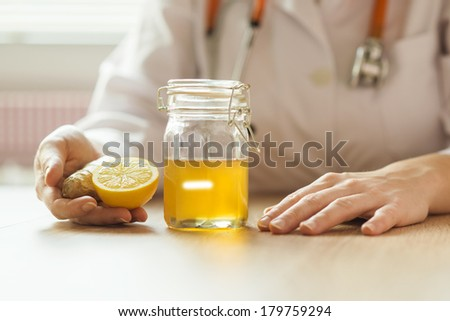Detail of honey and lemon with doctor woman in background