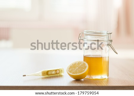 Detail of honey and lemon with sunny house interior in background