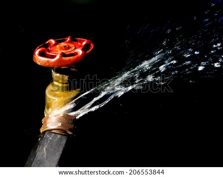 Detail of hose faucet connection leaking and squirting water spray - stock photo