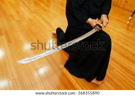 Detail of Japanese katana sword in hands of iaido fighter during training - stock photo