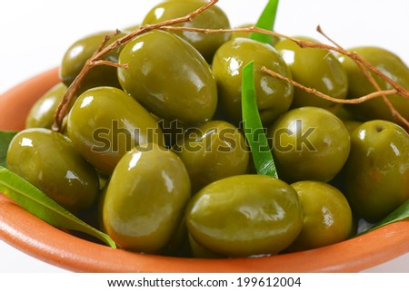 detail of juice green olives decorated with twigs and leaves - stock photo