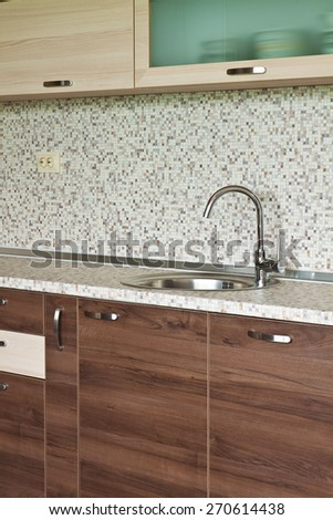 Detail of kitchen furniture with an emphasis on contemporary ceramic mixer cusine - stock photo