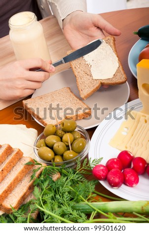 Detail of kitchen table and female hands spreading mayonnaise on sandwiches. - stock photo