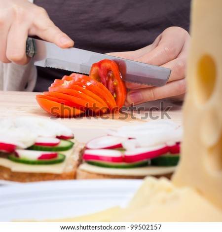 Detail of kitchen table female hands slicing fresh tomato.