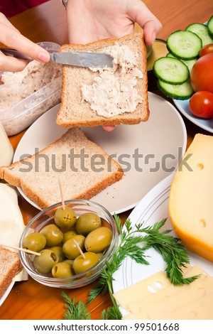 Detail of kitchen table with food and female hands making tuna sandwich. - stock photo