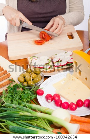 Detail of kitchen table with vegetable, sandwiches and female hands cutting fresh tomato.