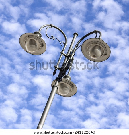 Detail of lamppost on cloudy sky background - stock photo