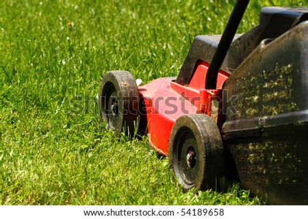 Detail of lawnmower on green grass in sunny day - stock photo