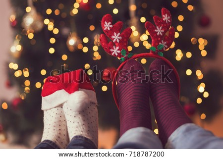 Detail of male and female feet wearing warm winter socks with small Santa's hat and antlers, placed on the table with Christmas tree and Christmas lights in background. Selective focus on the antlers