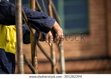 Detail of male Construction workers hands leaning over scaffolding