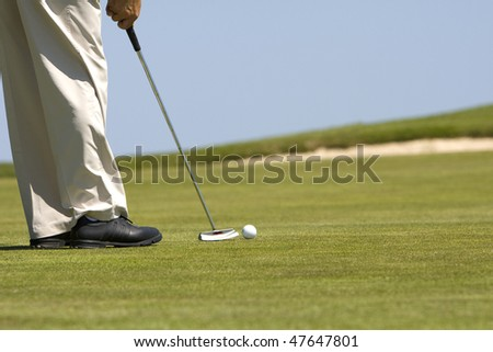 Detail of man playing golf on a fresh green golf course, drive and ball - stock photo