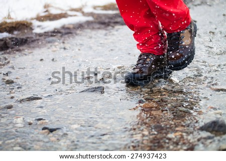 Detail of men's hiking boots walking through watery footpath in the mountains