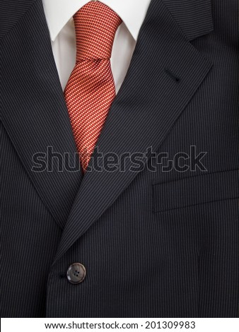 detail of mens pinstripe suit jacket lapel with  shirt and orange speckled tie