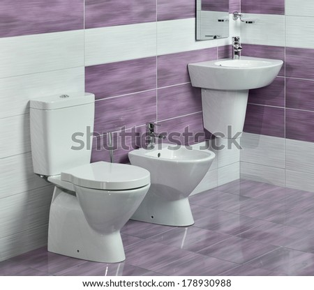 detail of modern bathroom with sink, toilet and bidet, with purple and white tiles and miror  - stock photo
