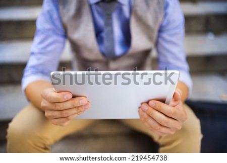 Detail of modern hipster businessman sitting on the stairs and using digital tablet - stock photo