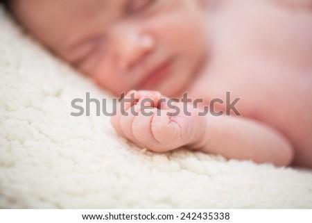 Detail of newborn baby hand sleeping - stock photo