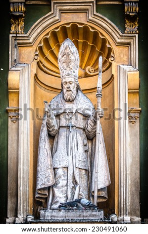 Detail of Nice Cathedral facade in close up view - catholic priest statue with staff in hand under yellow arch. Priest sculpture as part of church exterior. Architecture of Europe, France. - stock photo