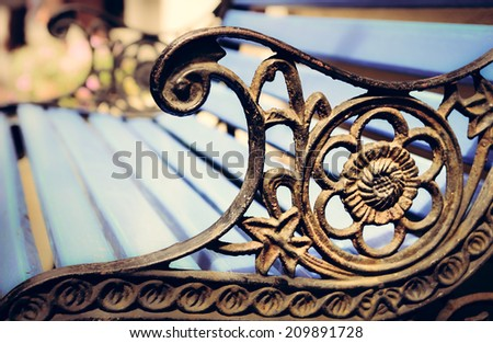 Detail of old park bench with ornaments and bokeh background, filtered vintage style
