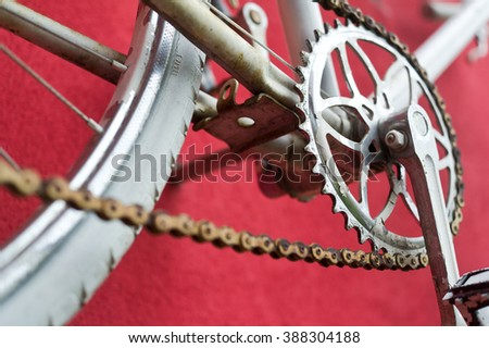 Detail of old road bike - crankset, pedal - on colorful red background. Shallow depth of field