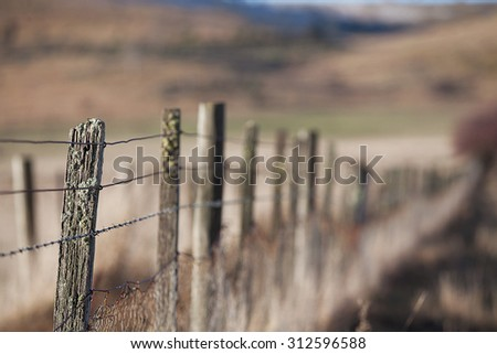Detail of old rural fencing with shallow focus on single fence post - stock photo
